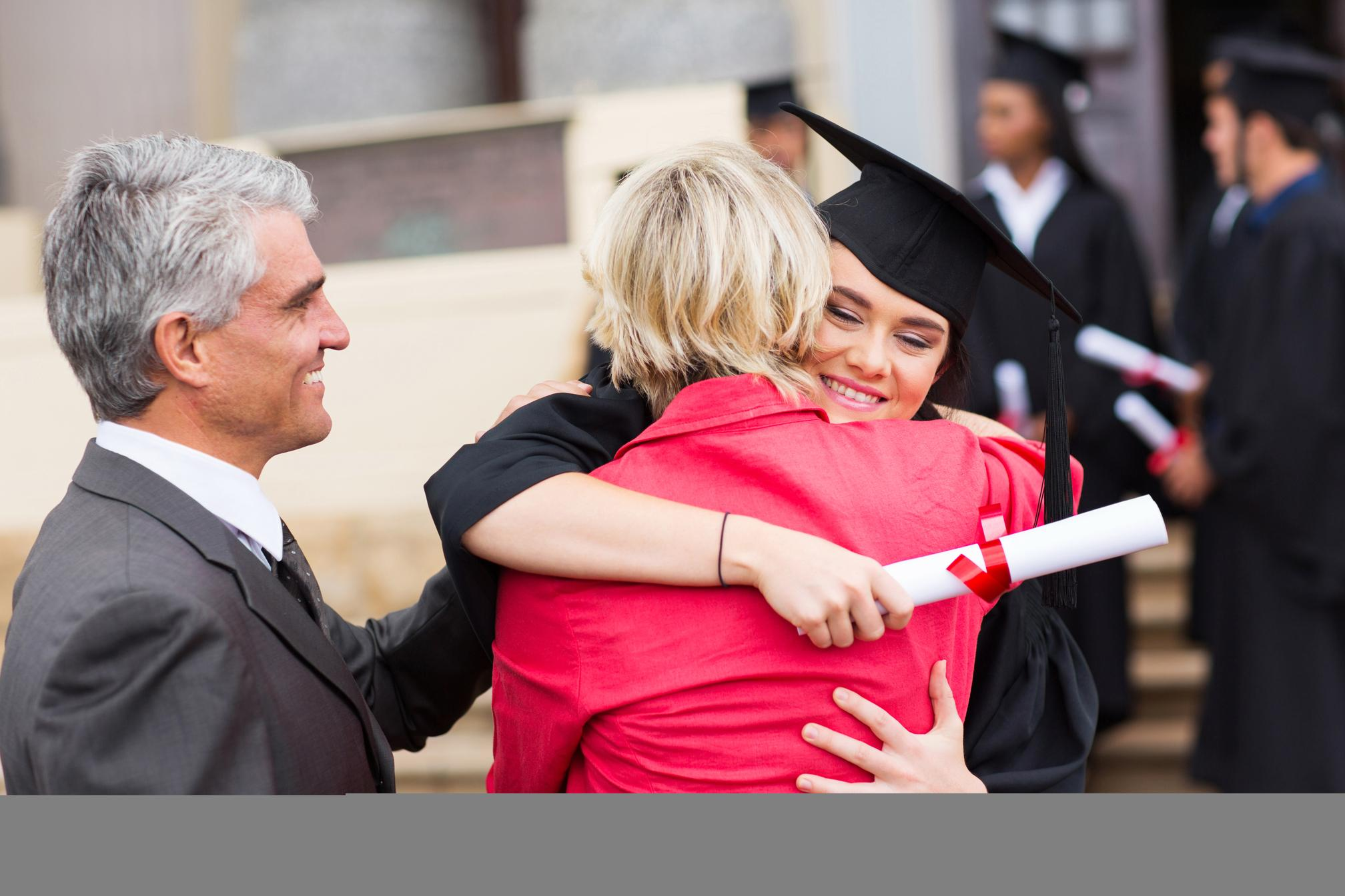 Female graduate hugging her family after graduation